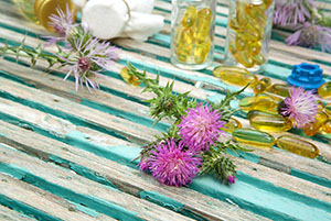 milk-thistle-blossoms-on-an-old-wooden-surface-milk-thistle-oil-in-softgels-in-the-background