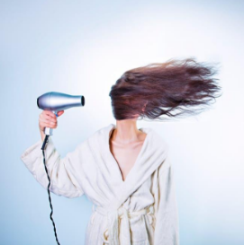 Woman in robe using hair dryer